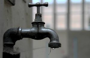 Photo of a disused tap with a solitary drip of water